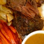 beef pot roast cooked in crock pot or slow cooker with carrots and onions and gravy