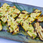 Fresh, yellow squash is grilled to perfection then drizzled with a bright, lemon chive vinaigrette for a delicious summer side dish.