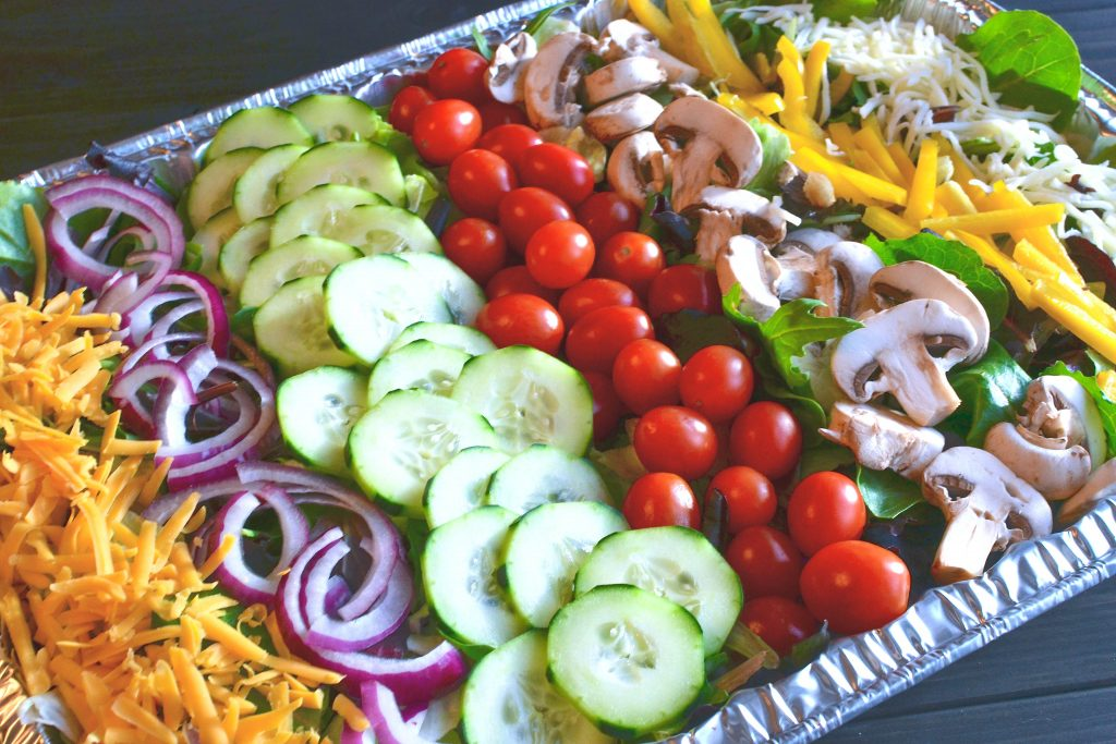 Salad for a crowd with tomatoes, cucumbers, onions, mushrooms and cheese with a homemade vinaigrette is a hit at any gathering or party.