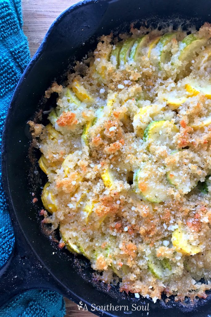 Squash casserole in cast iron skillet with cheese