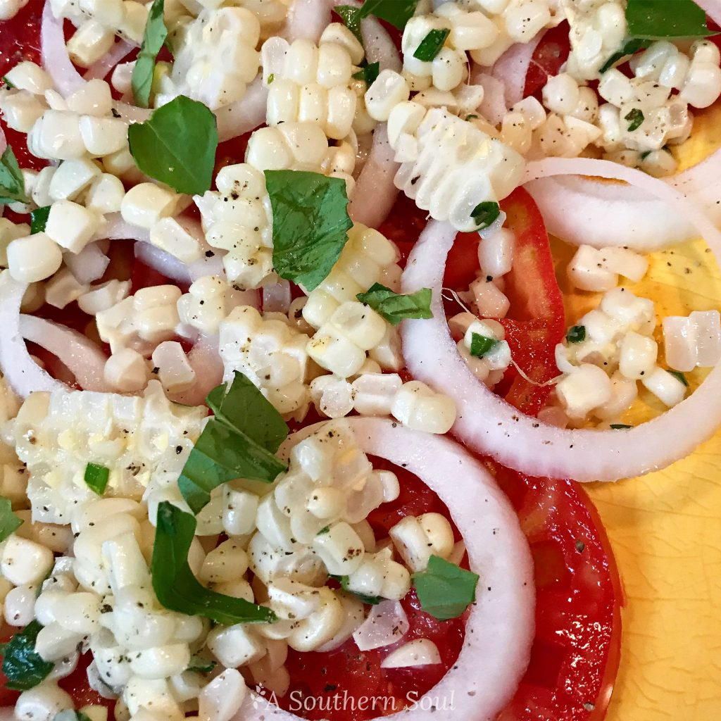 summer salad with tomatoes, onions, corn and herbs