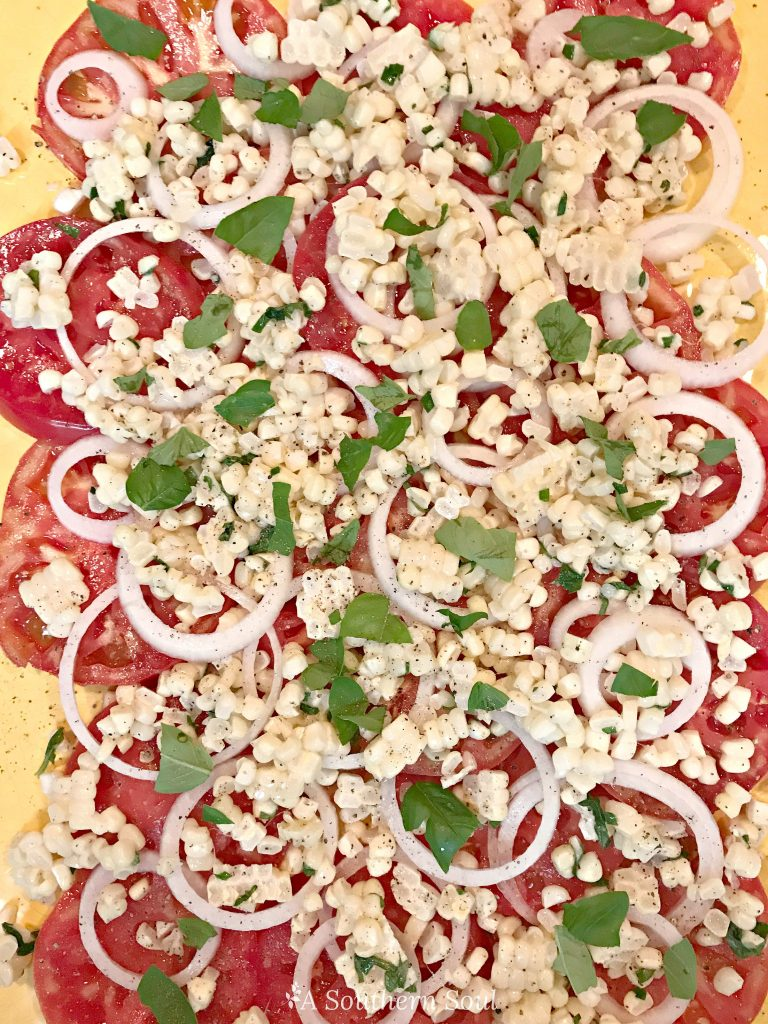 tomatoes, vidalia onion, corn, basil salad for summer on platter