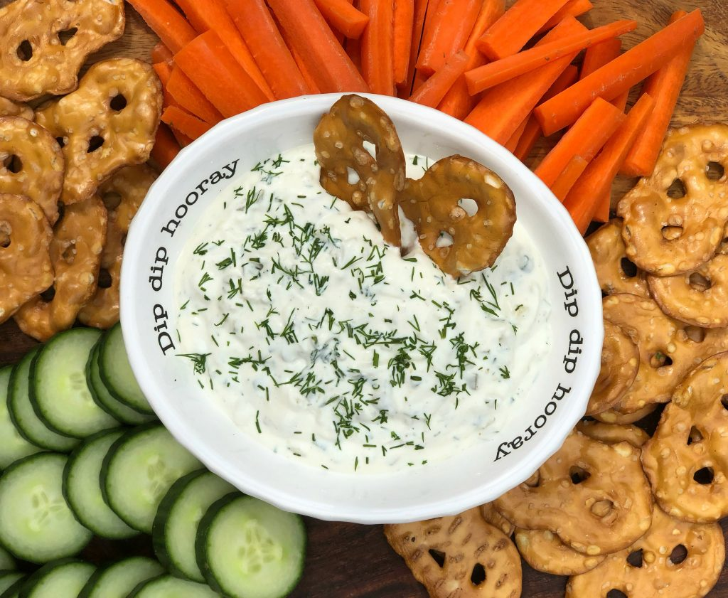 dill pickle dip with herbs served with veggies and crackers