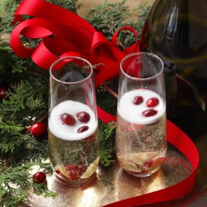 Make your holiday season extra bright with this signature cocktail! Mistletoe Mimosas, made with sparkling apple cider and Proscecco with chilled fruit is a great way to share a little holiday happiness.