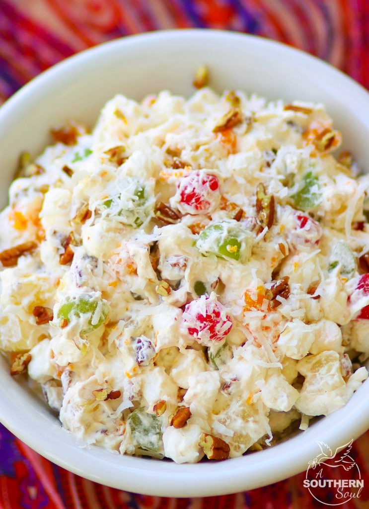 Ambrosia salad made with oranges, cherries, pineapple and marshmallows is tossed in a light fluffy mixture of fresh whipped cream with a touch of sour cream for extra flavor.