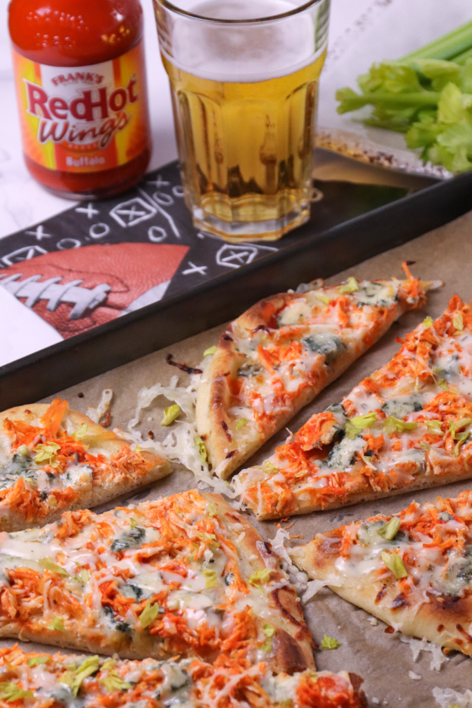 Buffalo Chicken Flatbread Pizza is great for gameday, parties or a quick and easy weeknight meal. Made with crockpot buffalo chicken, ranch dressing, blue cheese and topped with buffalo sauce.