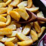 Cinnamon Apples cooked in a cast iron skillet using a wooden spoon.