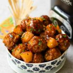 Crock Pot Hawaiian Meatballs in a bowl with the slow cooker and skewers.